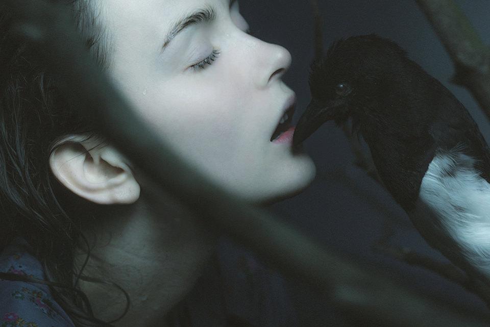 Ein bleiches Mädchen lässt sich von einem dunklen Vogelschnabel berühren.
