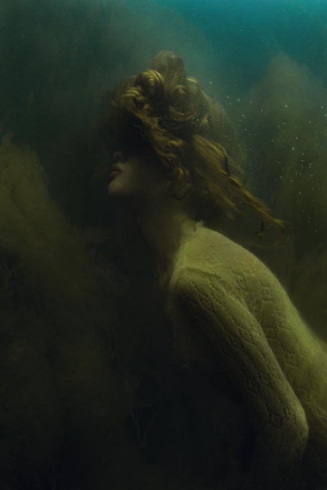 Eine Frau taucht im algigen Wasser.