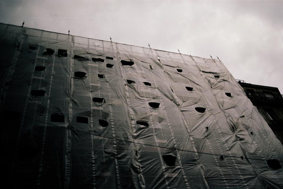 Die Folie um ein Hochhaus ist an vielen Stellen eingerissen.