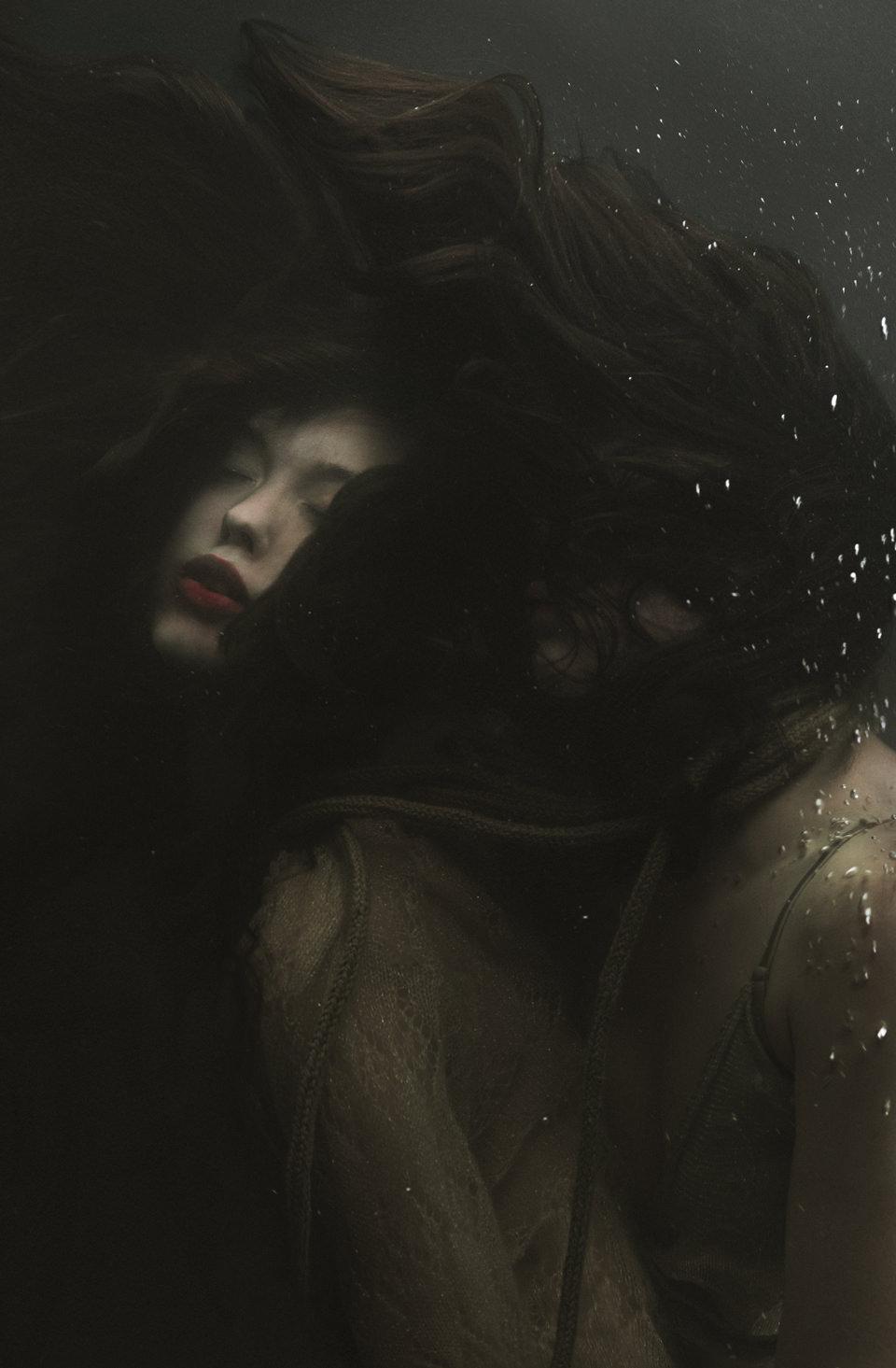 Eine Frau taucht und viele kleine Luftbläschen steigen auf.