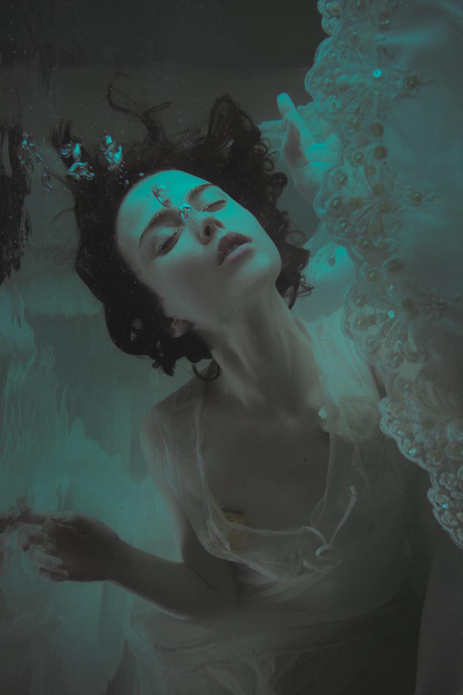 Eine Frau in weißem Kleid taucht und lässt Luftblasen aufsteigen.