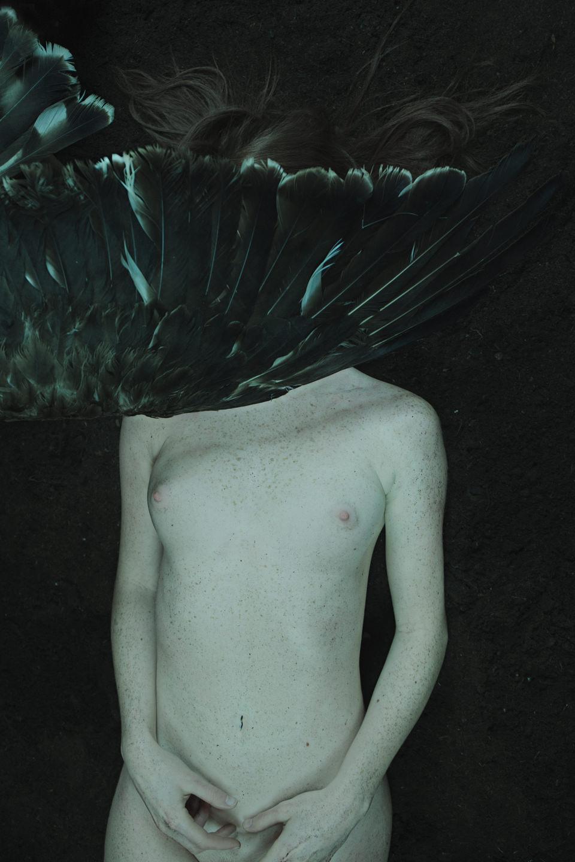 Der Flügel eines großen Vogels ist über dem Gesicht einer nackten Frau.