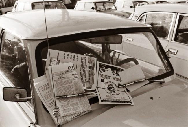 Verschiedene Zeitungen sind an der Windscheibe eines Trabis befestigt.