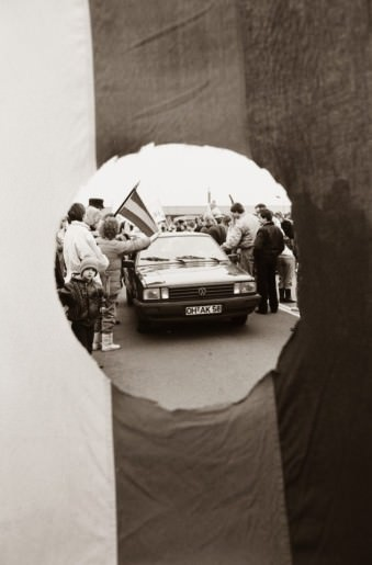 Ein von einer Menschenmenge umstelltes Auto, durch ein in eine Flagge geschnittenes Loch gesehen.