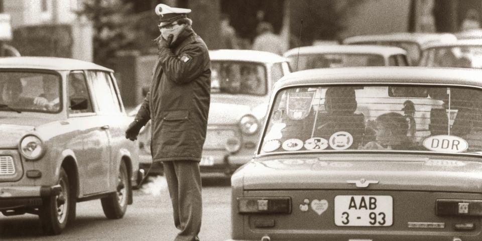 Ein Polizist steht auf der Straßen zwischen Trabis.