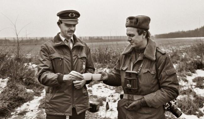 Zwei uniformierte Männer stehen in der Landschaft und stoßen an.