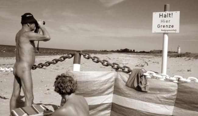 Ein nackter Mann sieht durch ein Fernglas über die bundesdeutsche Grenze an einem Strand, neben ihm sitzt eine Frau.