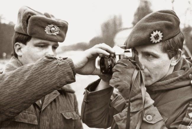 Zwei uniformierte Männer, einer sieht durch eine Kamera, der andere hilft ihm.