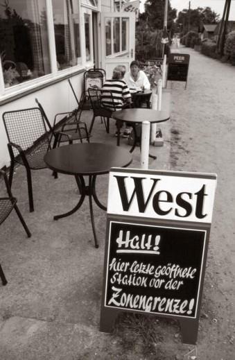 Werbetafel vor einem Lokal, im Hintergrund sitzen Menschen an einem der Tische.
