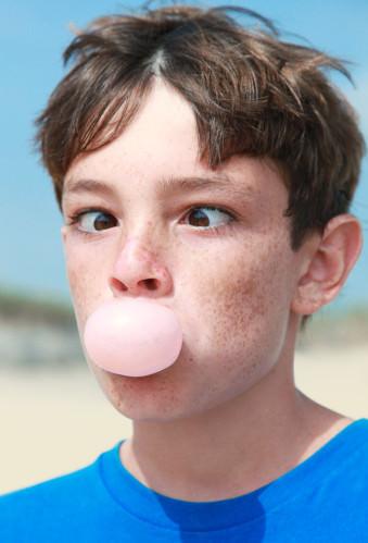 Ein Junge macht eine Kaugummiblase