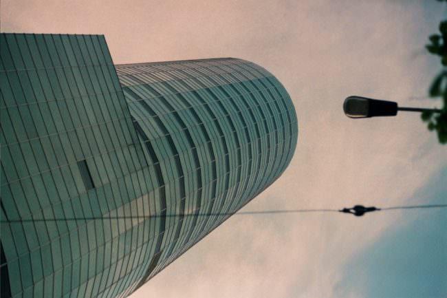 Blick an einem hohen Gebäude hinauf zu einem rosa Himmel, Oberleitungen kreuzen den Blick.