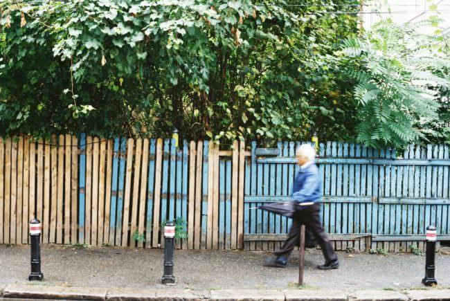 Ein Mann mit Schirm, unscharf in der Bewegung, geht vor einem bunten Holzzaun entlang.