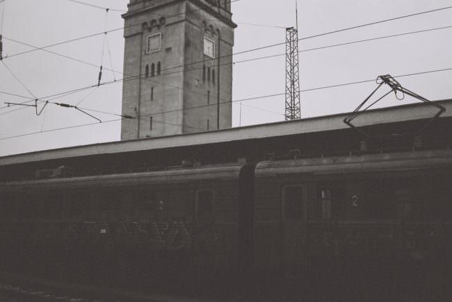 Ein dunkler Zug in einem Bahnhof, dahinter ragt ein Turm mit Ihren auf.