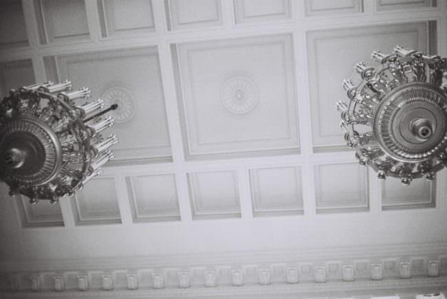 Zwei Kronleuchter an einer stuckverzierten Decke.
