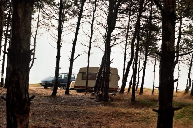 Auto mit Campinganhänger in einem Wald.