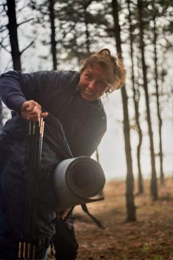 Eine Frau mit Rucksack, an dem Zeltstangen und eine Iso-Matte befestigt sind.