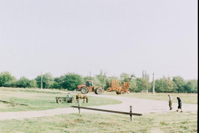 Eine Straßenszene auf dem Land mit einem Traktor, einer Person in einem von einem Pferd gezogenen Karren und zwei Fußgängern.