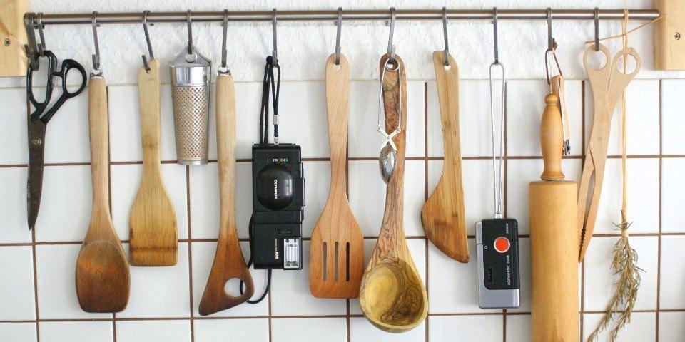 Zwei Kameras hängen zusammen mit Küchenutensilien an einer Hakenleiste.