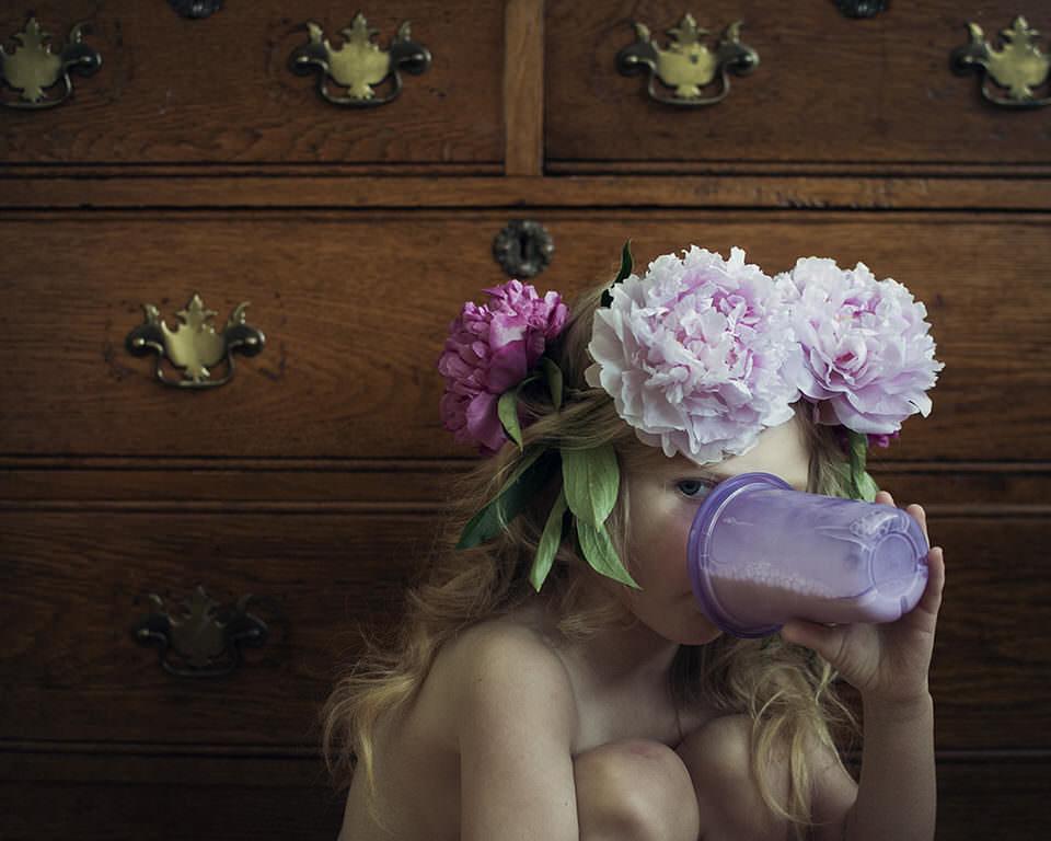 Ein Mädchen mit Blumenkranz trinkt aus einer Kinderflasche