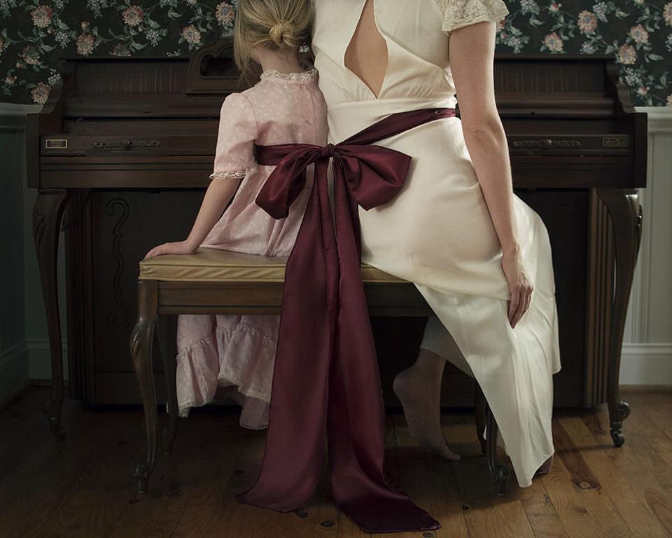 Frau und Kind mit einer Scheife zusammengebunden