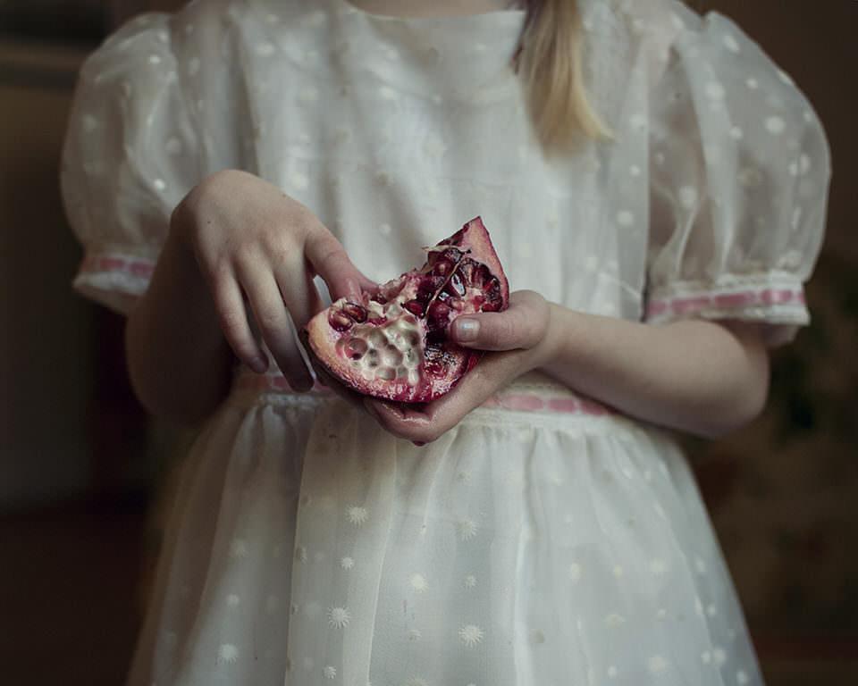 Ein Mädchen mit Granatapfel in Händen