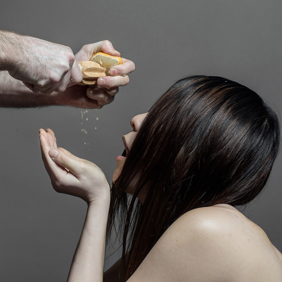 Eine Frau trinkt eine gerade gepresste Zitrone