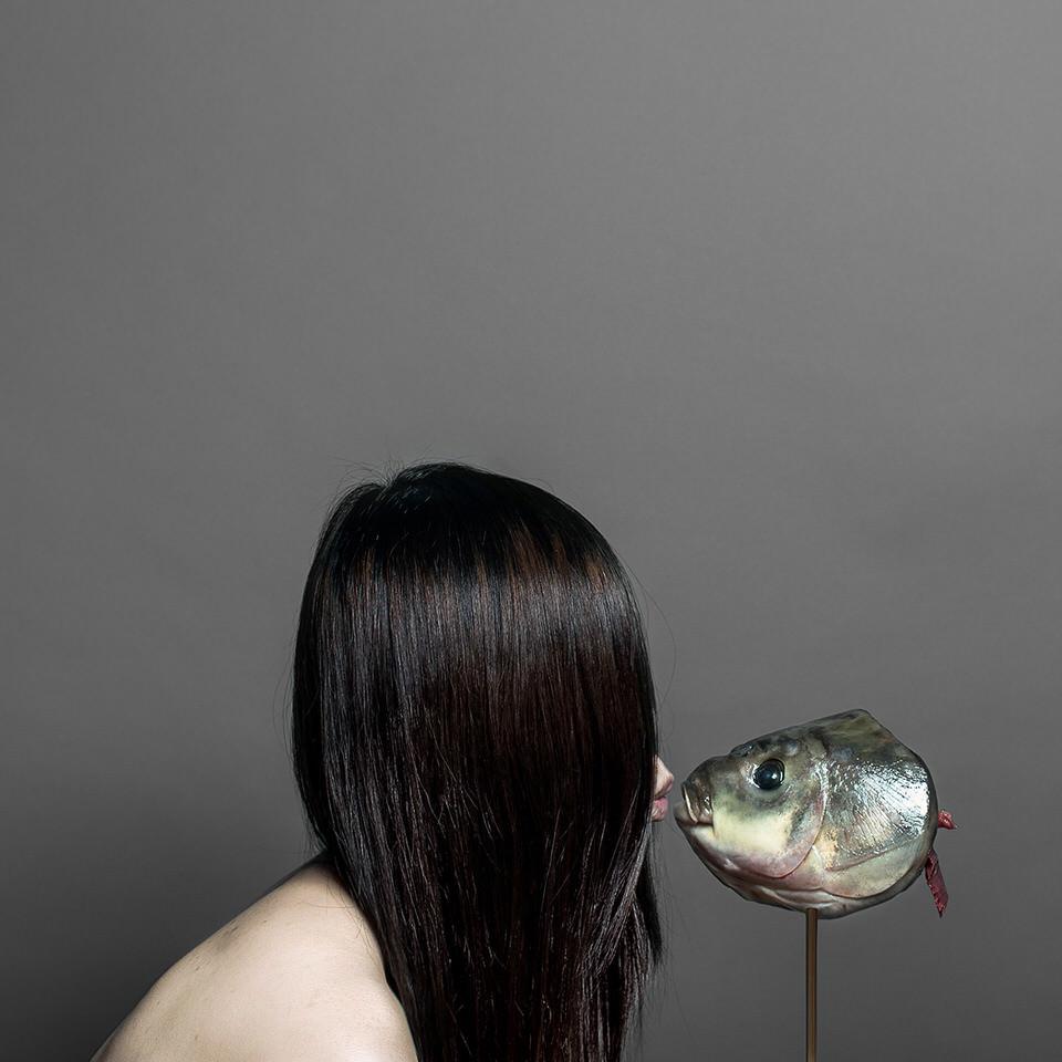 Eine Frau küsst einen Fischkopf