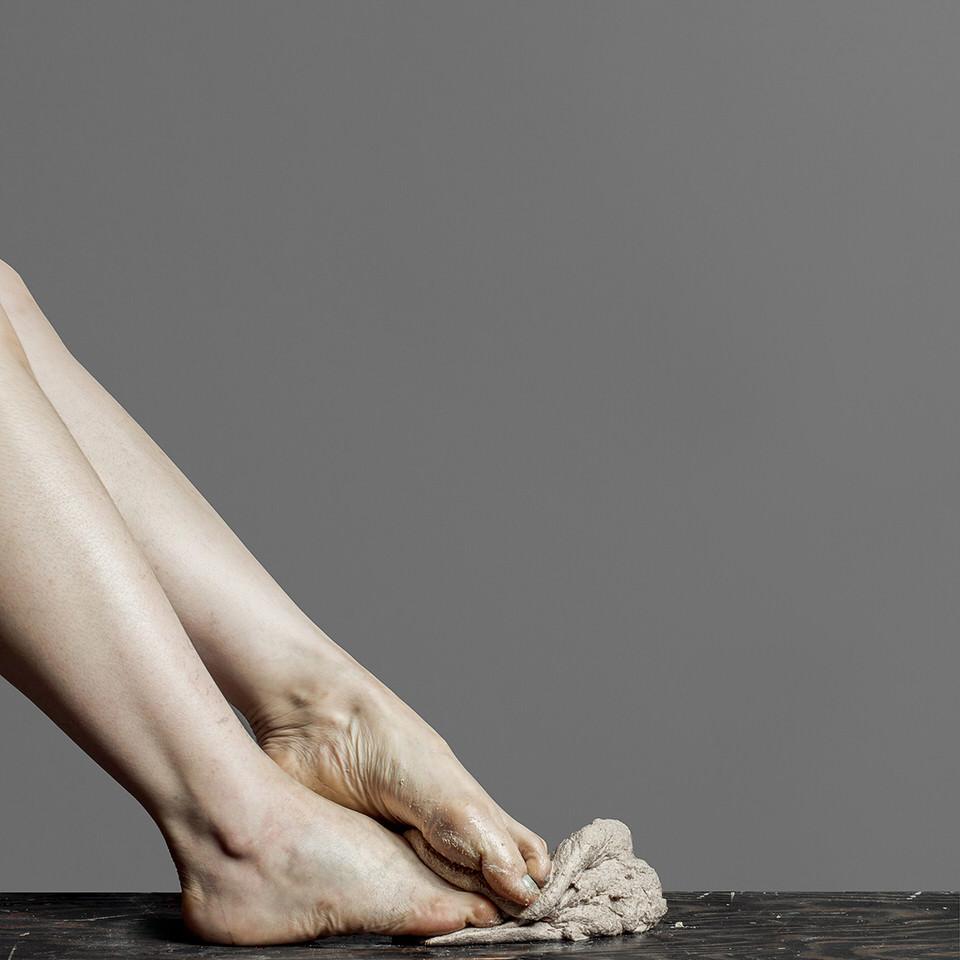 Füße zerdrücken eine graue Masse