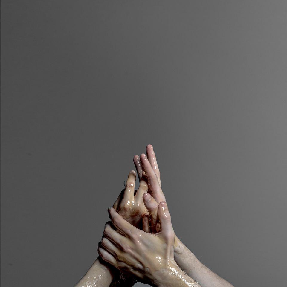 Vier Hände cremen sich mit Eimasse ein