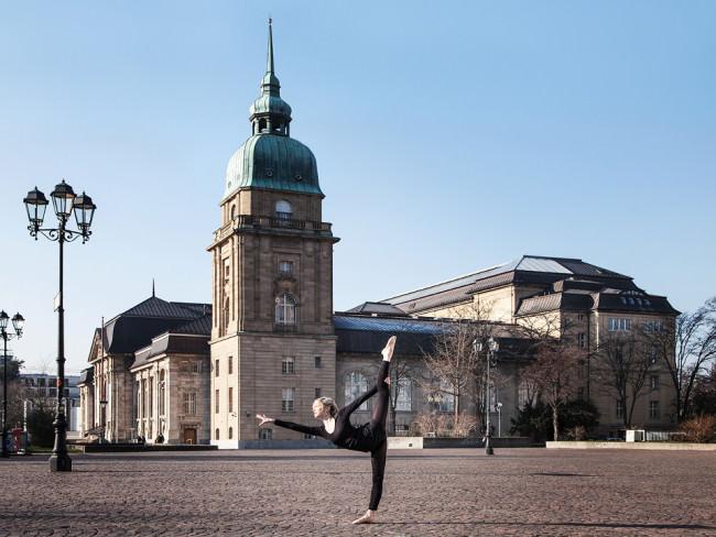 Eine Ballerina macht eine Figur vor einer Kirche.
