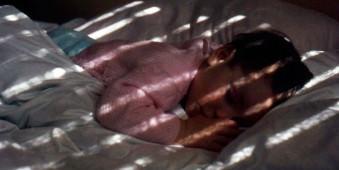 Ein schlafendes Kind, auf das Lichtstrahlen fallen.