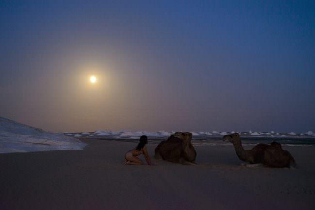 Eine nackte Frau und Kamele in einer Wüste.