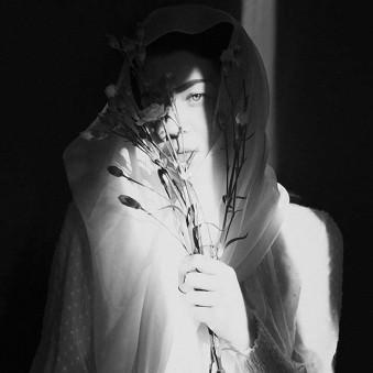 Verhülte Frau mit Blumen.