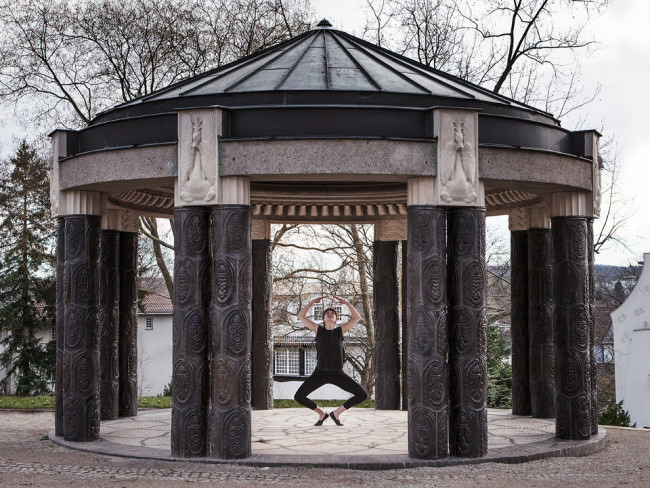 Eine Tänzerin in schwarzem Anzig springt unter einem Pavillion.