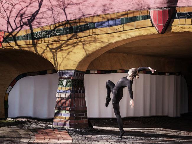 Eine Tänzerin verdreht ihren Körper unter einer Brücke.