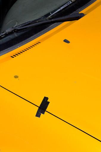 Eine gelbe Motorhaube mit schwarzem Klebeband