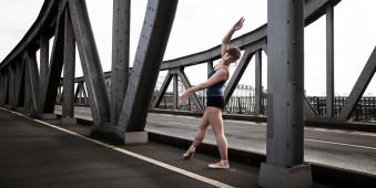 Eine Ballerina steht auf einer Brücke.