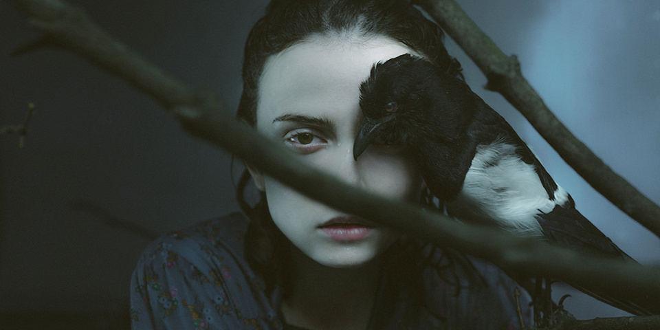Ein bleiches Mädchen hält einen Vogel vor ihr Gesicht.