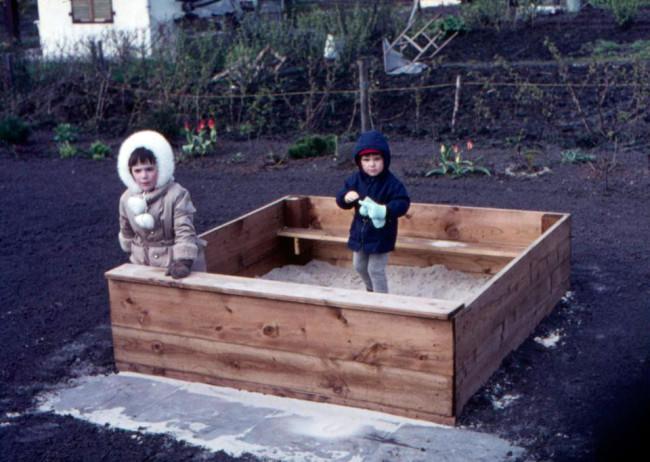 Zwei Kinder im Sandkasten.