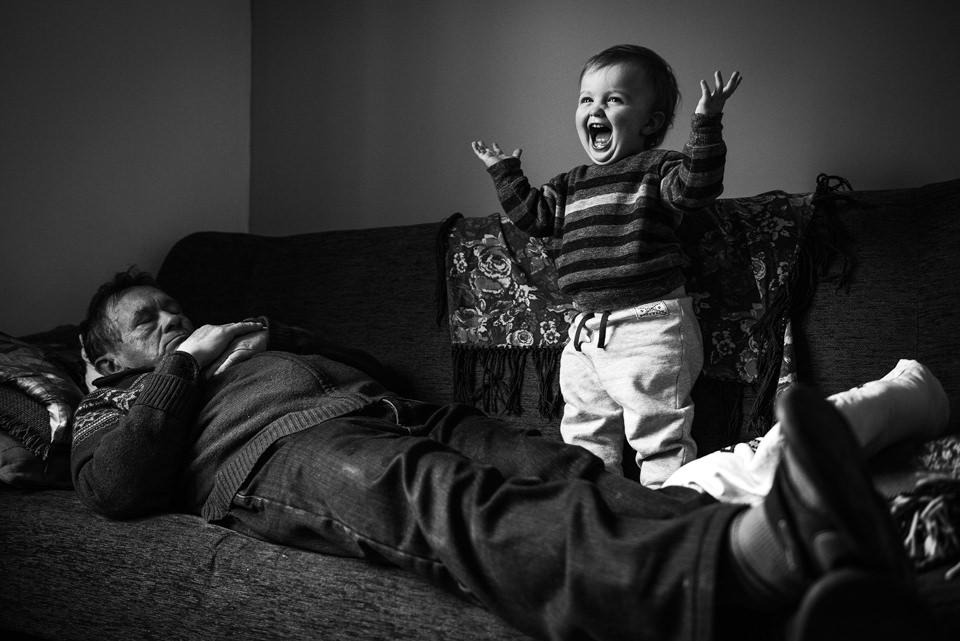 Ein Kind steht lachend auf einem Sofa