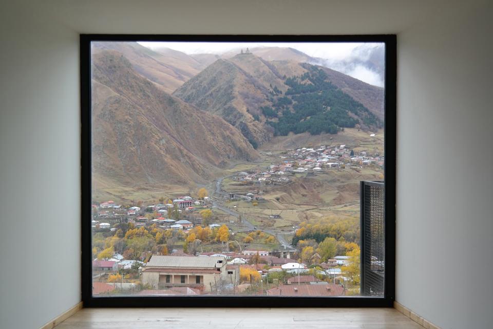 Sicht auf Stadt und Berge durch ein Fenster