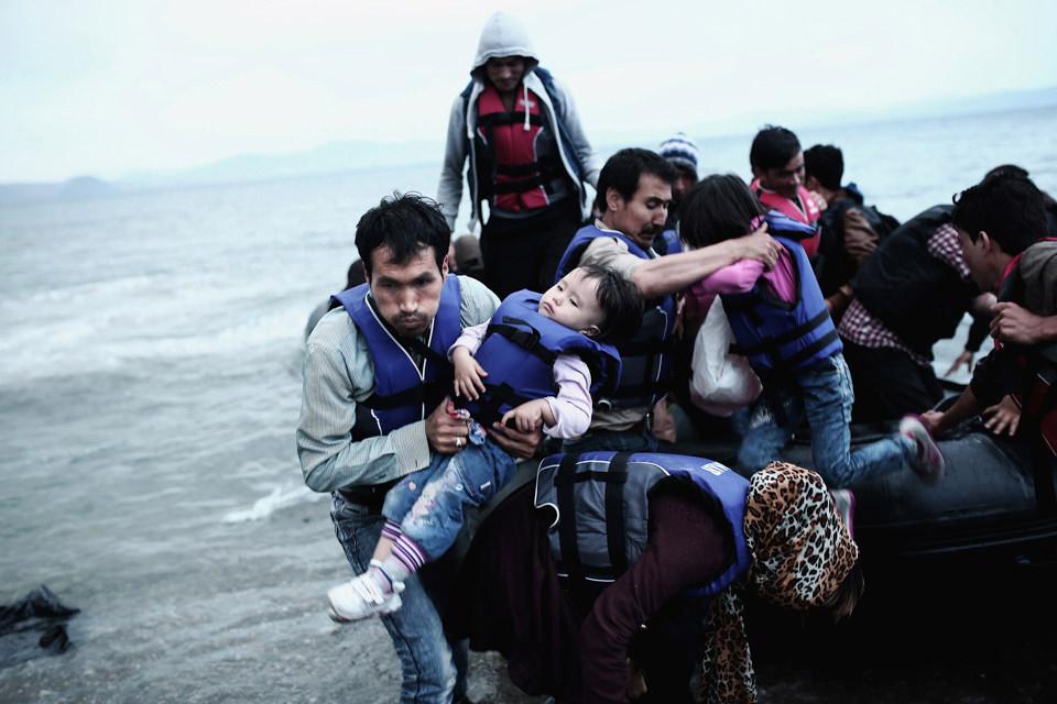 Ein Mann bringt ein Kind von einem Boot an Land
