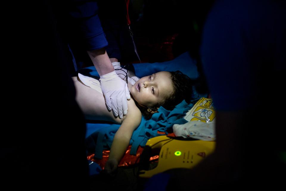 Zwei Hände mit Gummihandschuhen berühren eine kleines Kind