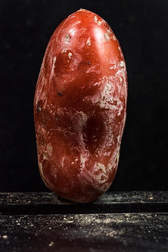 Eine Tomate vor schwarzem Hintergrund