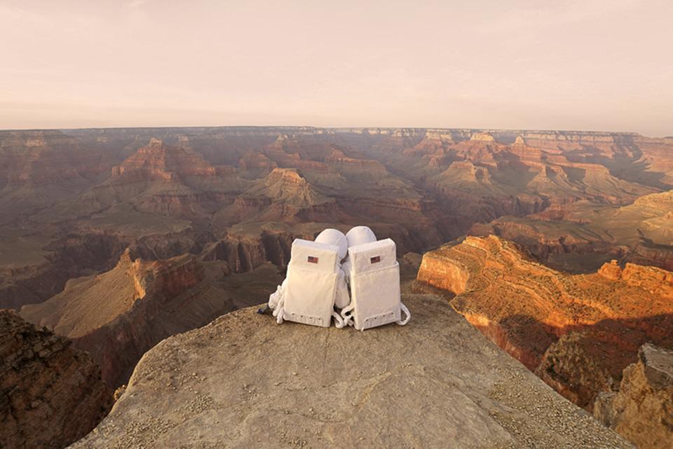 Zwei Astronauten sitzen aneinander angelehnt auf einem Fels