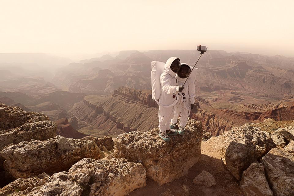 Zwei Astronauten stehen auf einem Fels und machen ein Selfie