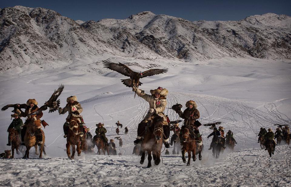 Eine Gruppe Personen reitet mit Adlern durch den Schnee