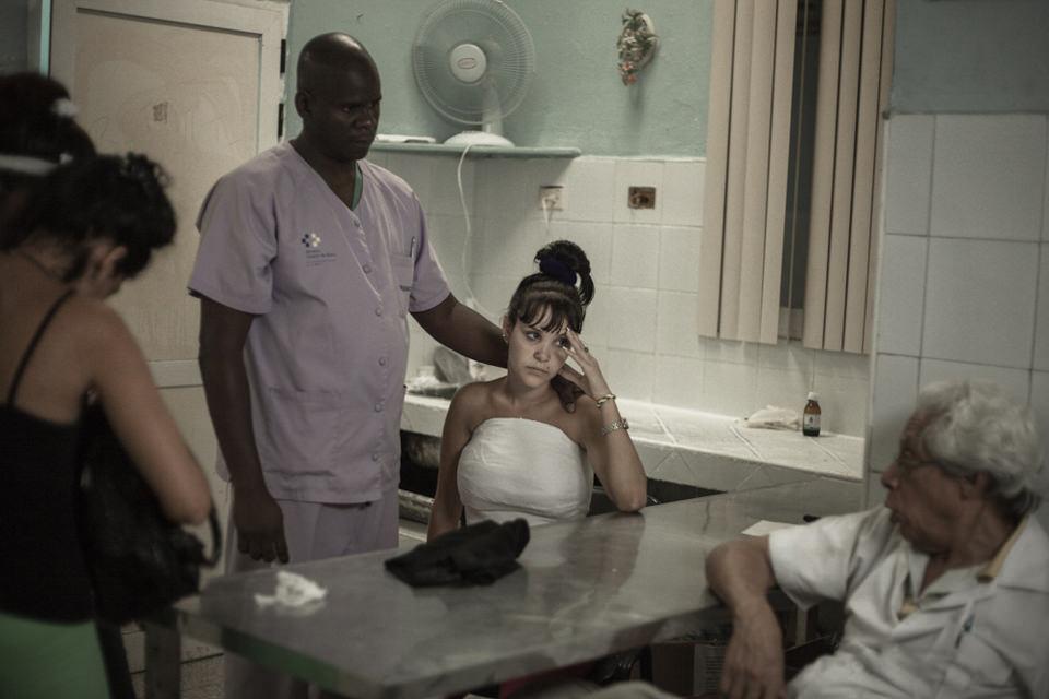 Mehrere Personen in einem Krankenzimmer, eine Frau trägt ein weißes Kleid.
