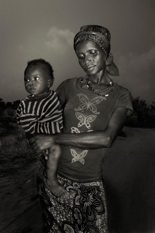 Schwarzweiß Portrait einer schwarzen Frau mit einem Kind auf dem Arm