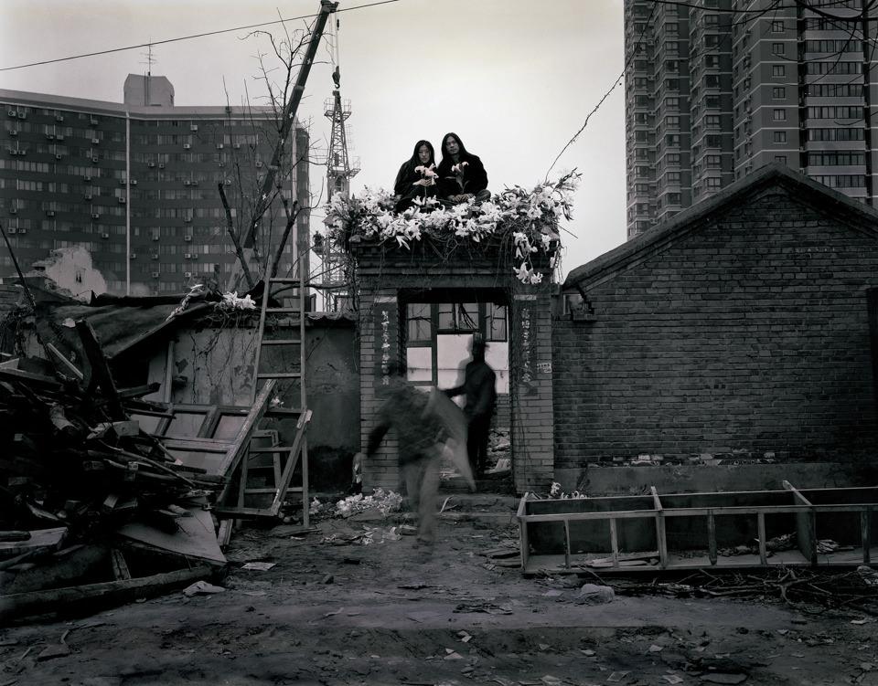 Zwei Personen sitzen auf einem Torbogen